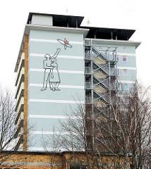 Hochhaus im Stadtteil Weststadt in Schwerin - in den 1960er Jahren erbaut; Fassadenschmuck, Mann / Frau Sputnik, roter Stern.
