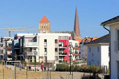 Neubauten / mehrstöckige Wohnhäuser auf dem Gelände des ehem. Güterbahnhofs Rostock; im Hintergrund die Kirchtürme der Nikolaikirche  und der Petrikirche.