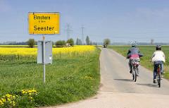 Schild Dorfende von Seester - Elmshorn 6km, Radfahrer in der Sonne - gelbes Rapsfeld im Hintergrund.