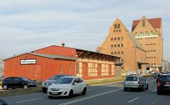 Historische Gebäude am Wornowufer im Stadthafen von Rostock, fahrende Autos.