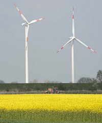 Blühendes Rapsfeld im Frühling - Windkraftanlagen, Rotorblätter - Trecker auf dem Feld; im Hintergrund der Deich an der Krückau.