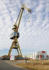 Ehem. Hafenkran, Werftkran der Neptunwerft im Rostocker Stadthafen; im Hintergrund Neubauten Wohnhäuser.