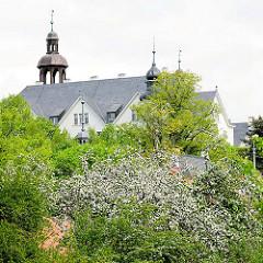 Blick über blühende Obstbäume zum Kupferturm des Plöner Schlosses.