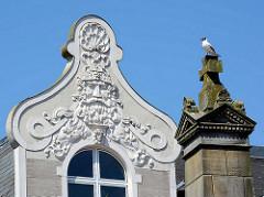 Aufwändiges Fassadendekor - Gründerzeitgebäude am Marktplatz in Eutin - eine Möwe sitzt auf der Spitze der Stele des Gefallenendenkmals.