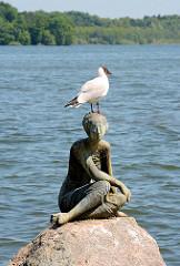 Bronzeskulptur DIE SCHAUENDE am Grossen Eutiner See; Bildhauer Karl Heinz Goedtke - eine Möwe sitzt auf dem Kopf der Figur am Seeufer.