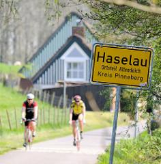 Ortschild Haselau, Ortsteil Altendeich - Kreis Pinneberg; Radfahrer auf der Deichstrasse - Wohnhäuser mit Reet gedeckt.