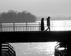 Fugänger an der Seepromenade in Plön - Licht spiegelt sich auf dem Plöner See.
