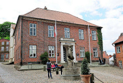 Historische Architektur in Plön - Plöner Rathaus, erbaut 1818 - Architekt Baumeister Christian Frederik Hansen; im Vordergrund  Muschelkalk Brunnen, Gänseliesel, Bildhauer Bernhard Butzke.