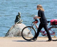 Bronzeskulptur DIE SCHAUENDE am Grossen Eutiner See; Bildhauer Karl Heinz Goedtke - eine Frau schiebt ihr Fahrrad auf dem Fussweg..