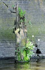 Reste eines Holzdalbens mit Gras, Löwenzahn und Farn bewachsen - Relikte / Überbleibsel vom alten Hamburger Hafen.