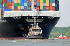Das Containerschiff CMA CGM MARGRIT läuft auf der Elbe in den Hamburger Hafen ein - ein Schlepper unterstützt das 366m lange und 48m breite Frachtschiff beim Manöver.