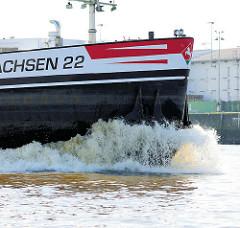 Das Binnenschiff Niedersachsen 22 in Fahrt auf der Elbe im Hamburger Hafen - Gischt am Schiffsbug.