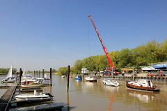 Beginn der Sportbootsaison im Haseldorfer Hafen - ein Segelboot wird mit einem Telekran ins Wasser gelassen.