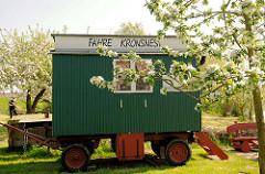 Holzwagen Aufschrift Fähre Kronsnest, blühende Apfelbäume an der Krückau in Neuendorf.