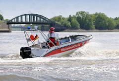 Ein Motorboot der Hamburger Wasserwacht in Fahrt auf dem Reiherstieg im Hafen - im Hintergrund die Kanalbrücke über den Veddel Kanal im Stadtteil Kleiner Grasbrook.