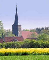 Kirchturm der Heilig Dreikönigs Kirche in Haselau, im 14. Jahrhundert errichtet - im Vordergund blühendes Rapsfeld / Rapsblüte.