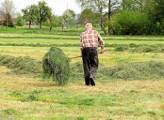 Ein Bauer wendet Gras / Heu mit einer Forke auf einer Wiese in Kollmar.