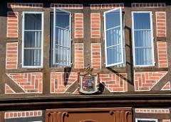 Fachwerkhaus, geöffnete Fenster - Wappen über dem Eingang.