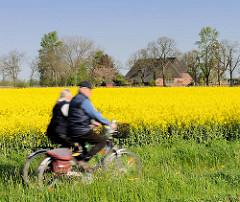 Fahrradfahrer / Paar, Mann und Frau auf Fahrrädern vor einem blühenden Rapsfeld in Haseldorf.