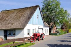 Wohnhaus mit Reet gedeckt - Traktor vor der Tür.