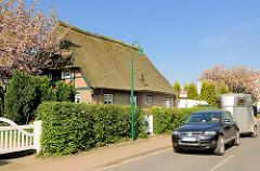 Reetdachhaus - Wohnhaus mit blühenden Kirschbäume - KFZ mit Pferdeanhänger.