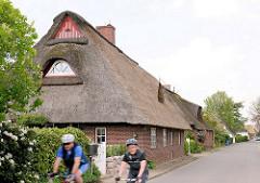 Wohnhaus mit Reetdach an der Strasse in Seestermühe - RadfahrerIn.