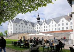 Aussengastronomie, Tische mit Gästen und Sonnenschirmen vor dem Plöner Schloss; das Schloss ist eines der größten Schlösser Schleswig-Holsteins, errichtet im 17. Jahrundert - Residenz der Herzöge von Plön; jetzt in Privatbesitz / gemeinnützige Stiftu