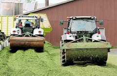 Walzschlepper / Traktoren mit Walze legt die Grasmiete auf einem Bauernhof in Kollmar an.