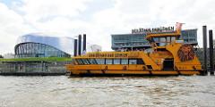 """Hafenfähre am Anleger König der Löwen - Shuttle Service zum Musical. Lks. das Gebäude """"Theater an der Elbe"""" in dem das Musical """"Das Wunder von Bern"""" aufgeführt wird."""