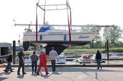 Beginn der Wassersportsaison im Haseldorfer Hafen - ein Segelboot wird mit einem Telekran angehoben.