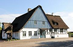 Restaurant / Cafegarten in Neuendorf - Reetdachgebäude; hellblau und weiss gestrichener Holzgiebel.