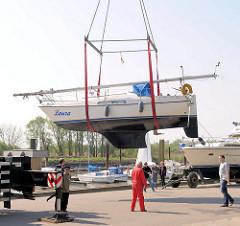 Beginn der Sportbootsaison im Haseldorfer Hafen - ein Segelboot wird mit einem Telekran angehoben.