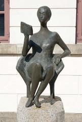 Die Lesende; Bronzeskulptur vor dem Gebäude der Eutiner Landesbibliothek im Kavaliershaus am Schlossplatz; Bildhauer Karlheinz Goedtke.