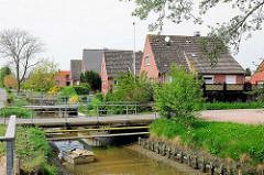Einfamilienhäuser mit Spitzdach an der Schulstrasse in Kollmar - Brücken führen über den Entwässerungsgraben zum Grundstücke.