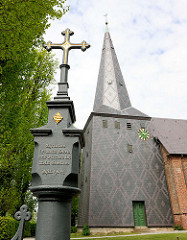 Dorfkirche in Kollmar, einschiffiger Backsteinbau aus dem 15. Jahrhundert. Schmiedeeisernes Kreuz am Friedhofseingang, Inschrift: Christus ist mein Leben, und Sterben ist mein Gewinn - Phil. 1, v. 21