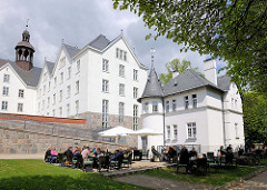 Aussengastronomie, Tische mit Gästen und Sonnenschirmen vor dem Plöner Schloss; das Schloss ist eines der größten Schlösser Schleswig-Holsteins, errichtet im 17. Jahrundert - Residenz der Herzöge von Plön; jetzt in Privatbesitz / gemeinnützige S