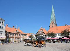 Marktplatz der Kreisstadt Eutin; links das Witwenpalais - re. die St. Michaeliskirche; Anfang des 13. Jahrhunderts als dreischiffige Basilika erbaut. Eine Pferdekutsche fährt über den Platz - Restaurant Tische unter Sonnenschirmen