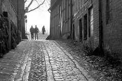 Historische Strasse mit Kopfsteinpflaster in Plön, Passanten - Schwarzweiss Motiv.