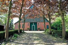 Kopfsteinpflaster, Ahornbäume mit jungen Blättern - historisches Bauernhaus in Neuendorf b. Elmshorn.