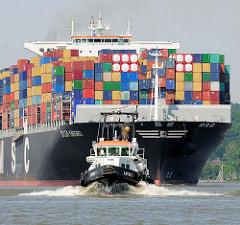 Der Containerfrachter CMA CGM MARGRIT hoch mit Containern beladen auf der Elbe vor Hamburg - das Lotsenschiff hat den Lotsen an Bord gebracht.