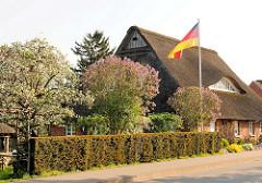 Reedachhaus - Wohnhaus in Haselau; blühende Bäume und Deutschlandflagge im Vorgarten.