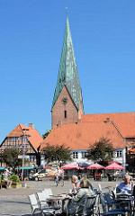 Tische eines Cafés und Restaurants in der Sonne auf dem Marktplatz von Eutin - Kirchturm der St. Michaeliskirche; Anfang des 13. Jahrhunderts asl dreischiffige Basilika erbaut.
