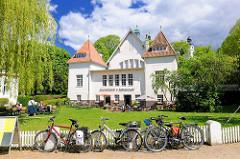Kulturforum Alte Schwimmhalle Plön; Aussengastronomie - Tische in der Sonne auf der Wiese; Fahrräder am Zaun - blauer Himmel, weisse Wolken