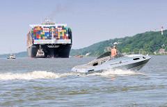Containerfrachter CMA CGM MARGRIT auf der Elbe vor Hamburg - ein schnelles Motorboot kreuzt die Fahrrinne.