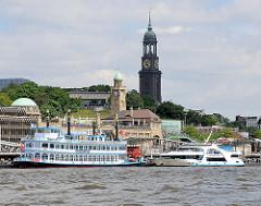 Blick auf die St. Pauli Landungsbrücken - Fahrgastschiffe, Raddampfer liegen für eine Hafenrundfahrt am Ponton - im Hintergrund die Hamburger St. Michaeliskirche / Michel, das Hamburger Wahrzeichen.