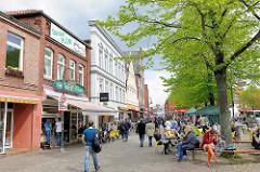 Fussgängerzone, Geschäfte und Passanten am Markt in Plön; Sitzbänke und Aussengastronomie.