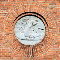 Relief / Dekor an der Fassade des Bauernhofs / Elbmarschenhaus - Symbole für Ernte / Korngarbe, Früchte - historische Erntewerkzeuge Sense, Rechen, Handpflug.