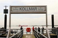 Schiffsanleger in Kollmar - Touristen auf dem Steg; ein Frachtschiff fährt elbabwärts.