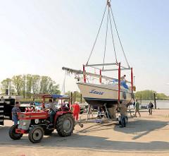 Saisonbeginn im Haseldorfer Sportboothafen - Bootstransport mit Trecker zum Kranen.