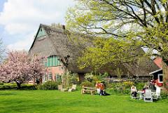 Bauernhaus mit Reet gedeckt, blühende japanische Zierkirsche - Tisch mit Gästen des Seestermüher Melkhus, Im Esch.